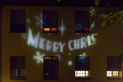 Pared de casa iluminada con la felicitación Merry Christmas del proyector LED