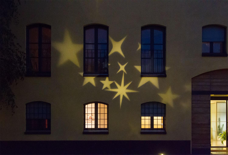 Pared de casa iluminada con el proyector de estrellas