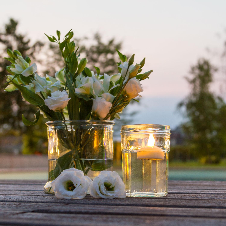 Blumenbouquet und Dekoglas mit Wasser und LED-Schwimmkerze