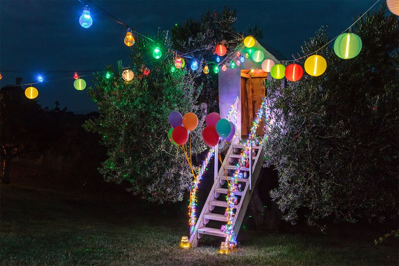 Guirlandes d'ampoules et de lampions decorant une fete d'anniversaire coloree