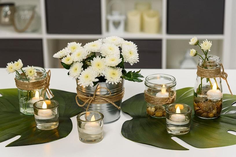 Centrotavola con candele led, fiori e vasetti di vetro