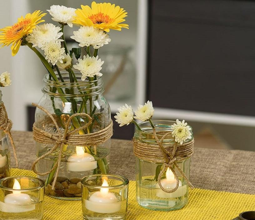 Vasetti di vetro con margherite e gerbere, candele led e pietre