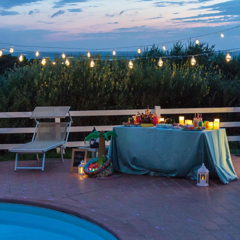 Allestimento tavolo con lampadine vintage per festa in piscina